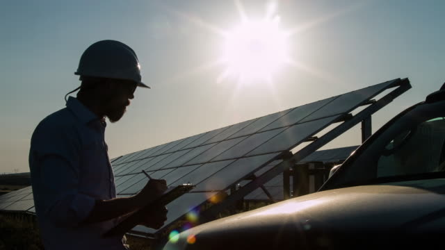 silhouette technician at solar power station - energy efficient stock videos & royalty-free footage