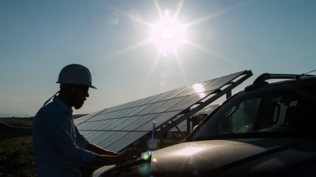 silhouette technician at solar power station - electrical component stock videos and b-roll footage