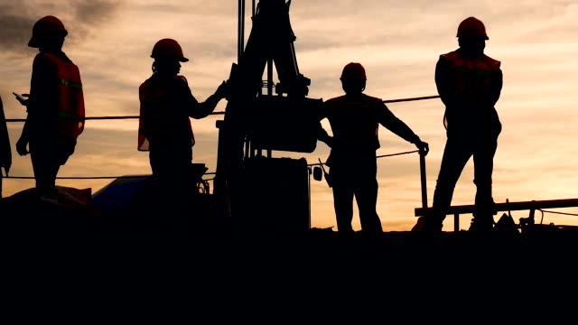 silhouette the group of workers working at a construction site.construction workers work in preparation for binding rebar and concrete work - building contractor stock videos & royalty-free footage