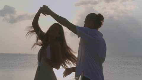 vídeos de stock, filmes e b-roll de silhueta para casais de 25 a 29 anos de idade, idade de etnia latino-americana e hispânica dançando com diversão ao longo da borda do mar do pôr do sol na praia de areia. férias - conceito istock. - wonderlust