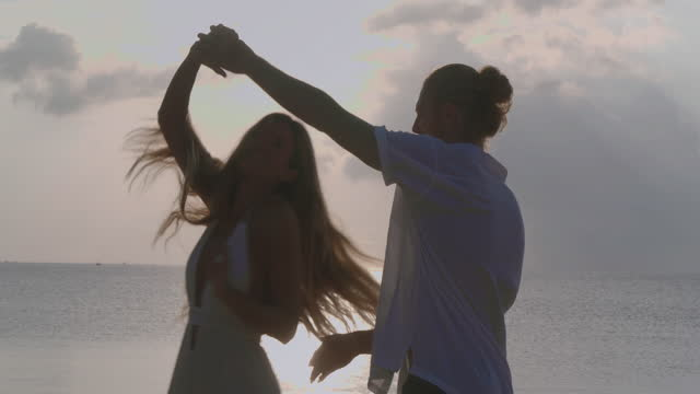 silhouette to couples age 25-29 yearold of latin american and hispanic ethnicity dancing with fun along edge of sunset sea on sand beach.vacations - istock concept. - wonderlust stock videos & royalty-free footage