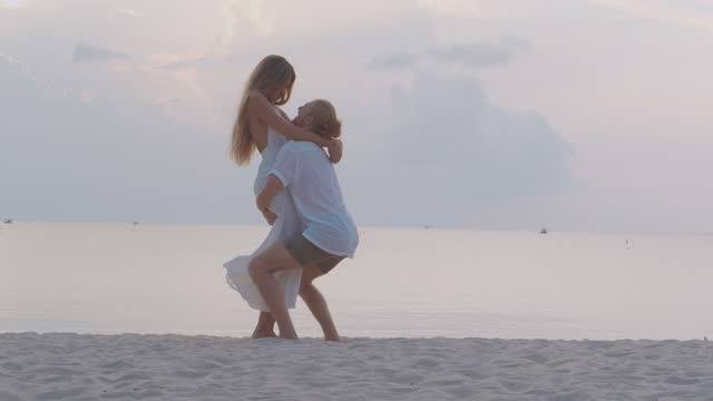 silhouette to couples age 25-29 yearold of latin american and hispanic ethnicity dancing with fun along edge of sunset sea on sand beach.vacations - istock concept.vacations - istock concept. - wonderlust stock videos & royalty-free footage