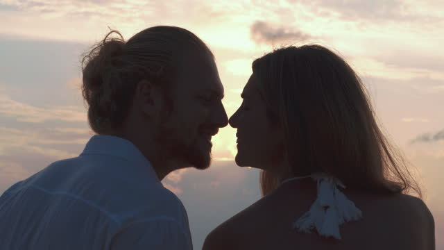 silhouette to couples age 25-29 yearold of latin american and hispanic ethnicity sitting and kiss with romance along edge of sunset sea on sand beach.vacations - istock concept. - wonderlust stock videos & royalty-free footage
