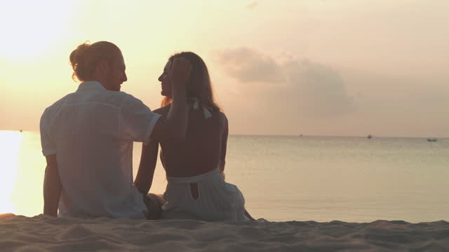silhouette to couples age 25-29 yearold of latin american and hispanic ethnicity sitting with romance along edge of sunset sea on sand beach.vacations - istock concept. - wonderlust stock videos & royalty-free footage