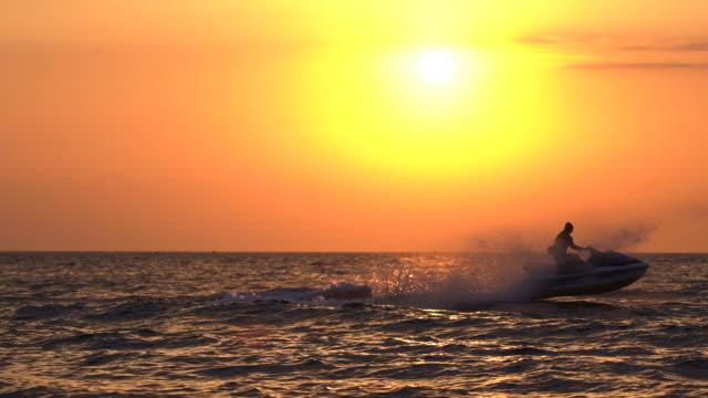 silhouette unrecognizable person riding jetski in the sea on sunset - acquascooter video stock e b–roll