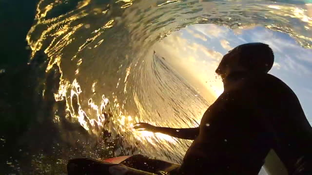 pov silhouette view of a surfer surfing waves on a surfboard and the sun with sunset. - slow motion - surf stock videos & royalty-free footage