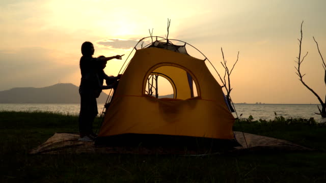 silhouette view: women trying to set a tent together on waterside on sunset - tent stock videos & royalty-free footage