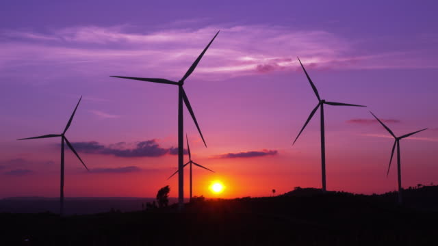 silhouette wind turbines farm at sunset - wind turbine stock videos & royalty-free footage