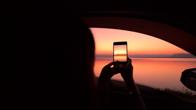 silhouette woman enjoy taking a photo view sunset over lake in the car, slow motion - photography video stock e b–roll