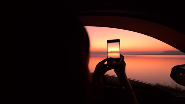 silhouette frau nehmen einen foto blick auf sonnenuntergang über see im auto, slow-motion - passagier stock-videos und b-roll-filmmaterial