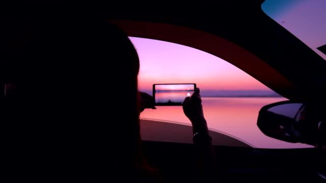 vídeos de stock, filmes e b-roll de mulher de silhueta desfrutar tomando um por do sol do modo de exibição de foto sobre lago no carro - panorâmica