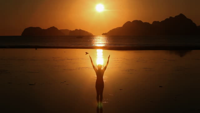 WS, silhouette woman standing in shallow waters raising and lowering arms at sunset with tropical island background / Corong Corong Beach, Bacuit Archipelago, El Nido, Palawan, Philippines