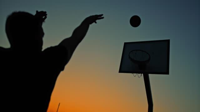 vidéos et rushes de ms super slow motion silhouette jeune homme tirant des cerceaux sur le terrain de basket-ball extérieur au crépuscule - plan en travelling
