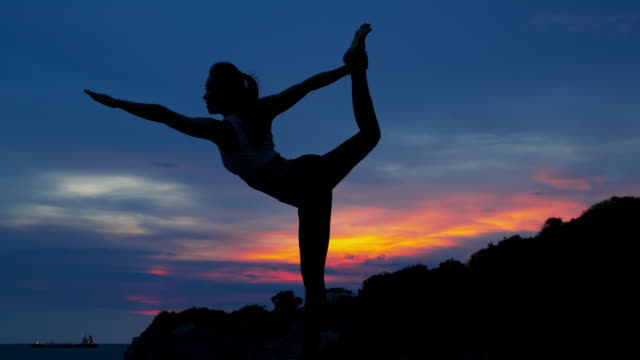 silhouette young woman is practicing yoga at mountain sea. - yoga stock videos & royalty-free footage