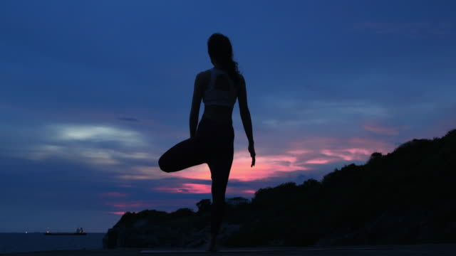 silhouette young woman is practicing yoga at mountain sea. - silhouette stock videos & royalty-free footage