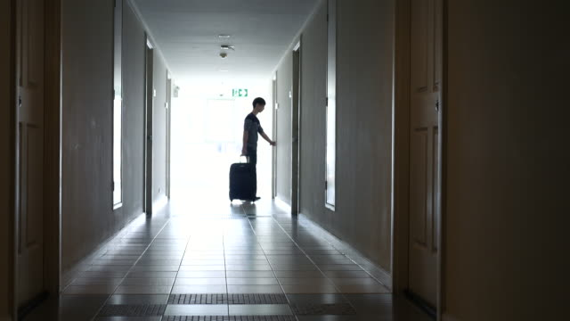 Silhouette youngman walking with luggage into the room