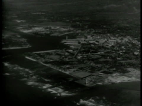 stockvideo's en b-roll-footage met silhouetted airplanes in flight aerial coastal area cu front of airplane in flight rounded nose td ws over bombs falling toward ground wwii - 1943