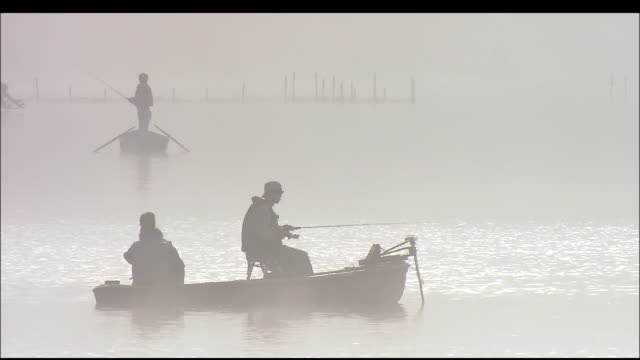 Silhouetted anglers fish from boats on Five lakes of Mount Fuji, Yamanashi