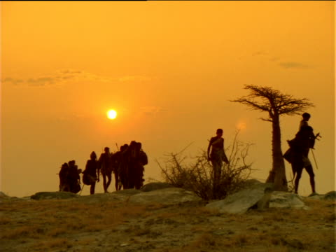 Silhouetted Basarwa tribes people walk along rocky landscape at sunset