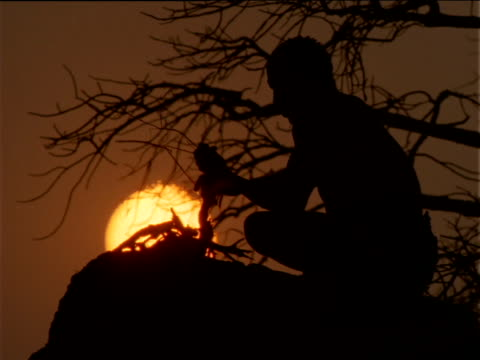 Silhouetted Basarwa tribesman sits on top of rock adding twigs to small fire, Botswana