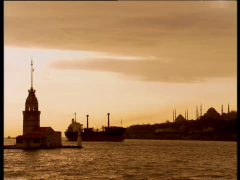 vidéos et rushes de silhouetted boat comes into harbor in evening light turrets and domes of mosques in distance istanbul - turquie