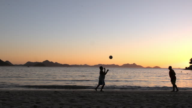 Silhouetted Brazilian men volley soccer ball back and forth by the water on Copacabana Beach at dusk