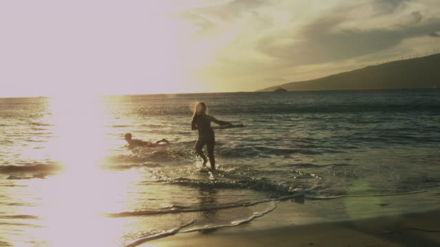 silhouetted brother and sister going out to surf in the ocean. - brother stock videos & royalty-free footage