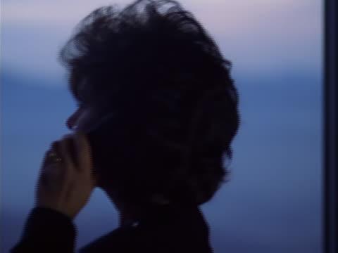 vídeos de stock e filmes b-roll de silhouetted businesswoman with phone - telefone sem fio
