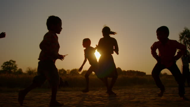 vidéos et rushes de silhouetted children play in countryside near varanasi, uttar pradesh, india. - inde