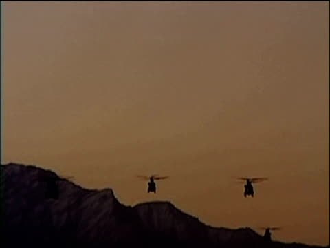 Silhouetted Chinooks flying over mountains towards camera Afghanistan 2002
