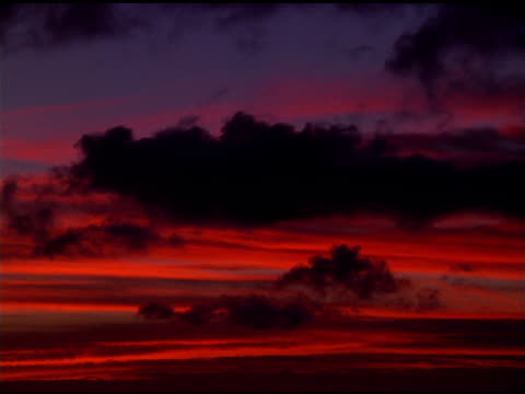 silhouetted clouds moving in front of red wispy clouds, kauai - wispy stock videos and b-roll footage
