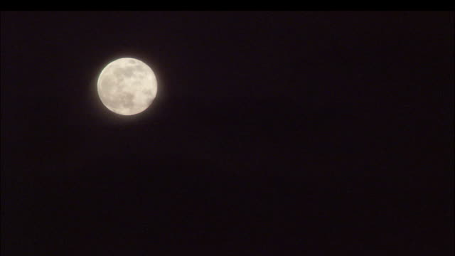 silhouetted clouds pass in front of a bright full moon. - transilvania video stock e b–roll