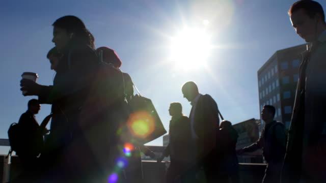 vidéos et rushes de les banlieusards silhouettes marchant, le ciel bleu et la lumière du soleil. - costume habillé