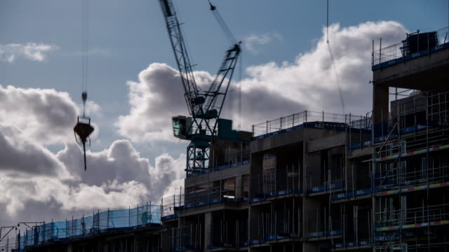 a silhouetted construction crane lifts and pours concrete on a construction site as rapidly moving clouds build and darken in the background - housing development stock videos & royalty-free footage