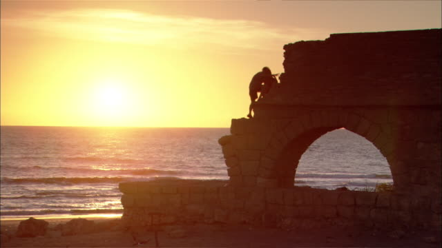 a silhouetted couple climbs the caesarian ruins against a gold sky. - arch architectural feature stock videos and b-roll footage