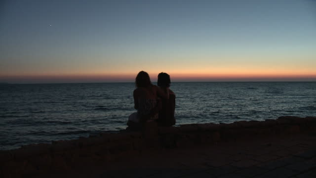 ms silhouetted couple sitting by sea at dusk / puzu idu, italy - controluce video stock e b–roll