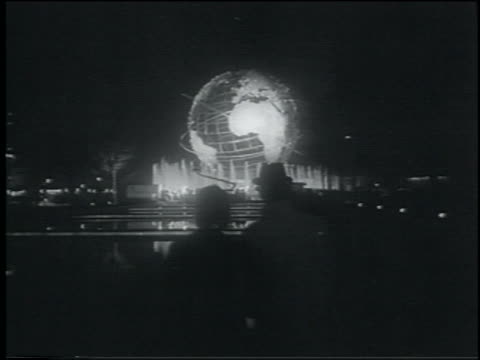 view silhouetted couple viewing unisphere in distance at night / ny world's fair - esposizione universale di new york video stock e b–roll