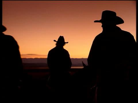 stockvideo's en b-roll-footage met silhouetted cowboys on horseback below orange sky cowboys move past camera wyoming - agrarisch beroep