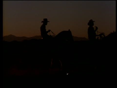 Silhouetted cowboys on horses trotting through desert, Mexico