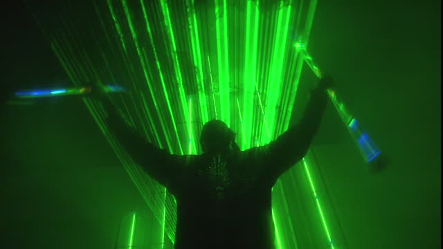 vídeos de stock e filmes b-roll de a silhouetted dancing man twirls glowing sticks in front of green beams of laser light. - arte, cultura e espetáculo