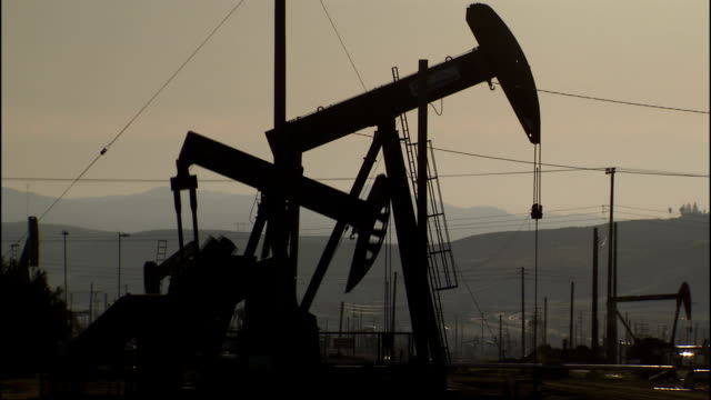 silhouetted derricks operate in an oil field. - industria petrolifera video stock e b–roll