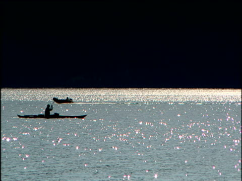Silhouetted dingy and kayak cross on Lake Laberge Yukon River Canada