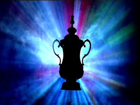 Silhouetted FA cup amidst strobe lighting and smoke