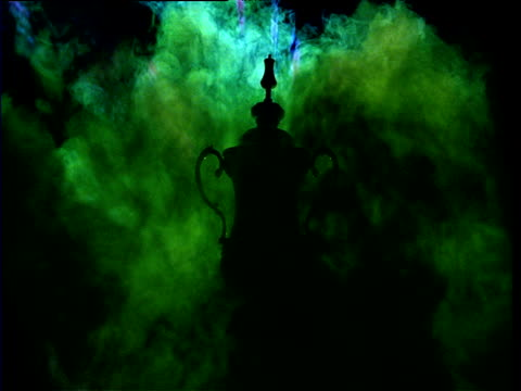 Silhouetted FA cup amidst swirling green smoke