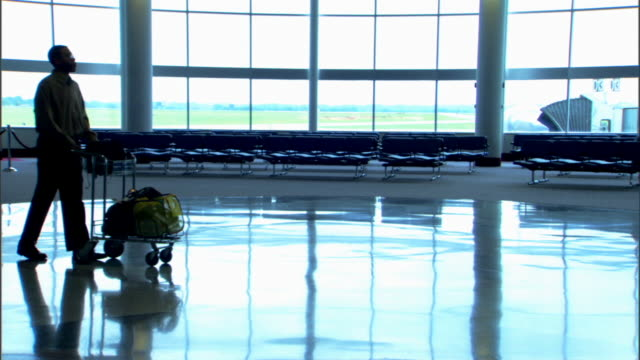 A silhouetted family walks through the airport with a cart of luggage and the son following behind.