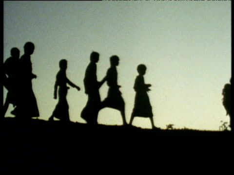 Silhouetted figures wearing hats and carrying yokes walk across land against white sky Burma