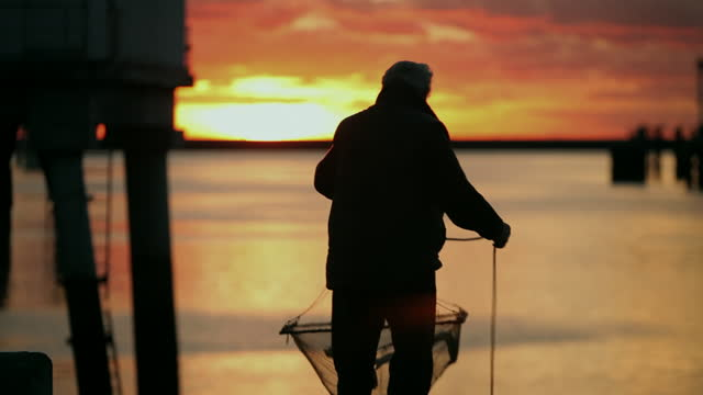 silhouetted fisherman at sunrise, france - fisherman stock videos & royalty-free footage