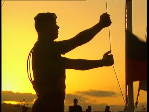 silhouetted french foreign legionnaires raise tricolour and djibouti flags at dawn parade with golden sky in background - hochziehen stock-videos und b-roll-filmmaterial