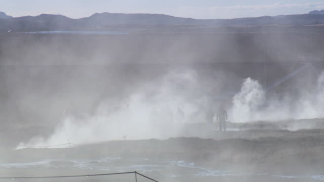 A silhouetted group of tourists, obscured by steam, leaves a geothermal field in Iceland.