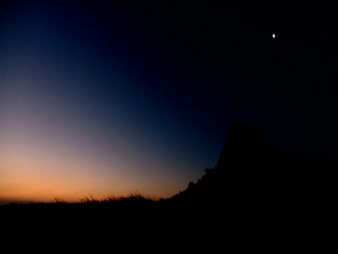 silhouetted hill in orange and blue evening light half moon in sky - half moon stock videos & royalty-free footage